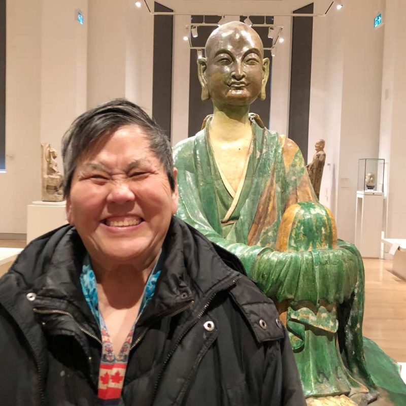 Participant in front of Buddha statue at the ROM